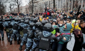 A  line of police in riot helmets and body armour face off against protesters in a Moscow street