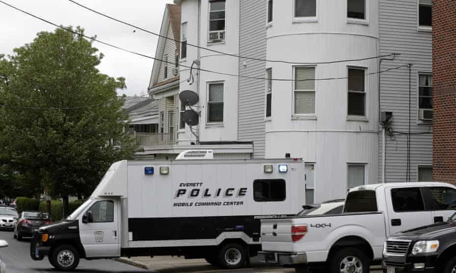 Police vehicles sit in front of a multi-storied home on Tuesday in Everett, Massachusetts, being searched by authorities in connection with a man shot and killed earlier in the day in Boston.