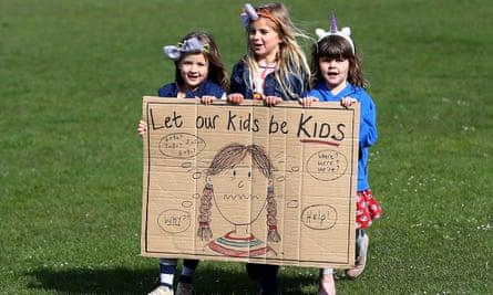 Schoolgirls hold a placeard – 'Let Our Kids Be Kids'