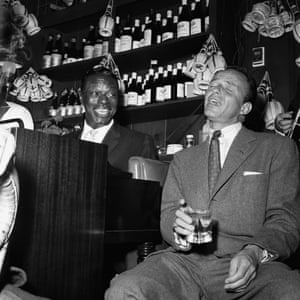Nat King Cole and Frank Sinatra belt out a tune at a party at the Villa Capri restaurant, Los Angeles, 1955.