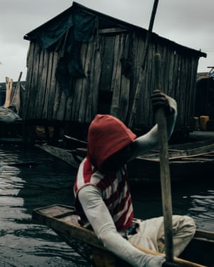 A young man using a canoe in Makoko.