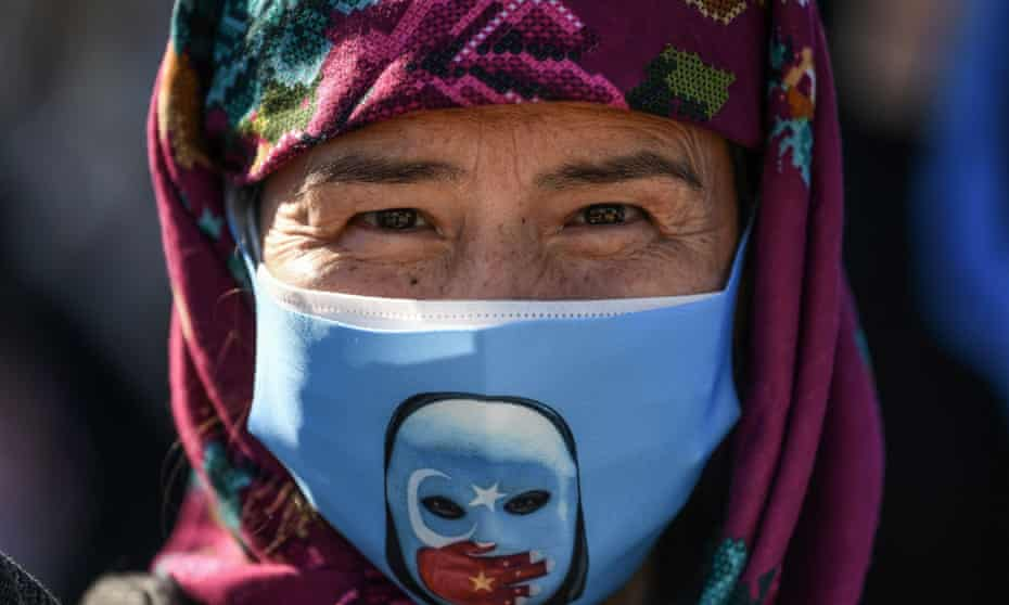 A supporter of China's Muslim Uighur minority wears a face mask with the flag of East Turkestan