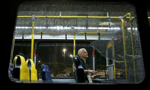 A person sits on an official media bus after a window shattered when driving accredited journalists at the Rio 2016 Olympic Games in Rio de Janeiro on Tuesday.