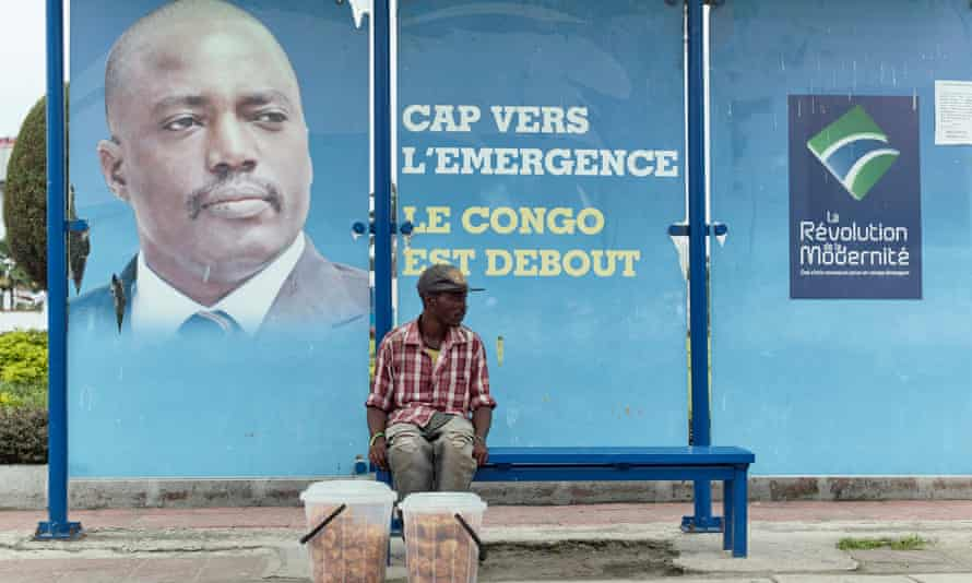 A vendor at a bus stand in Kinshasa in front of a picture of President Joseph Kabila.