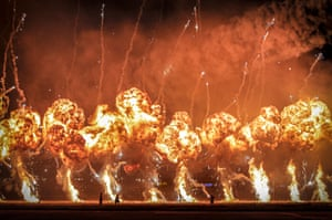 Bucharest, Romania: Technicians are silhouetted by pyrotechnics during an international air show