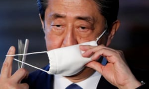 Japan's prime minister Shinzo Abe takes off his face mask as he arrives to speak to the media on Japan's response to the coronavirus outbreak.