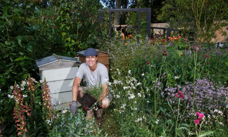 Marie-Louise Agius surrounded by wild flowers next to beehive