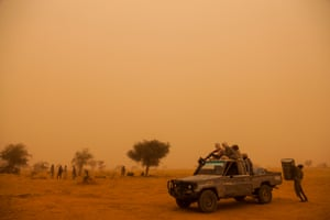 Rebel soldiers from the SLA leave their camp to find water in the middle of a sand storm in north Darfur