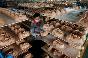 A worker checks a mask in quality control
