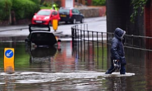 A man carries his shoes as he walks through flood water on Crossley Road in Greater Manchester.