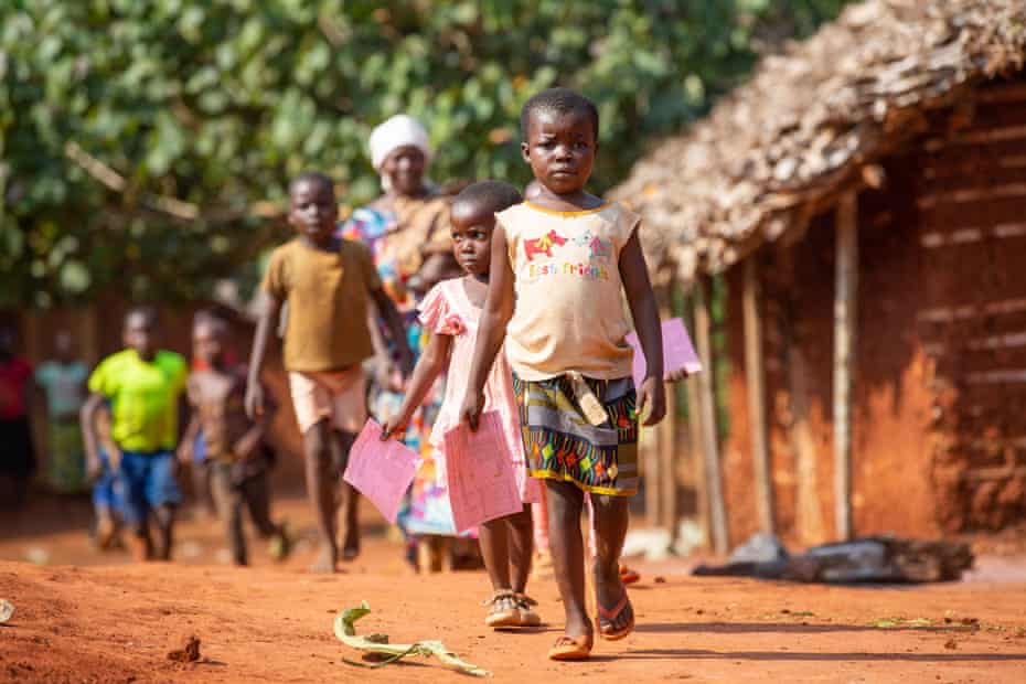 Mother and children walk home after getting vaccinated against measles in Lisaka, a remote village in DRC's Northern Mongala Province.