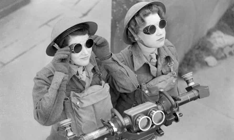 ATS spotters, wearing sunglasses, watch for any sign of hostile aircraft at a London anti-aircraft battery. In front of them is a range-finder.
