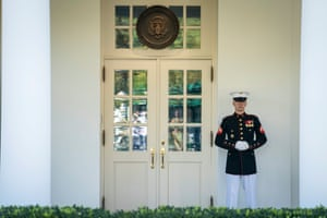 A Marine is seen on duty outside of the West Wing door, indicating Trump is in the Oval Office.