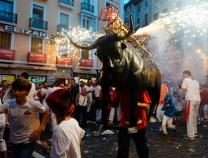 A man dressed as a toro de Fuego (bull of fire) chases people through the streets of Pamplona