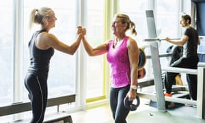 A lady in her late fifties works out with a female fitness trainer in the gym