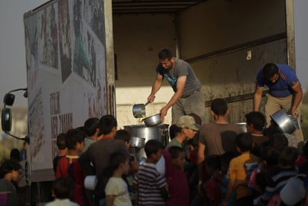 Internally displaced refugees wait in line for food aid in the northern Aleppo countryside.