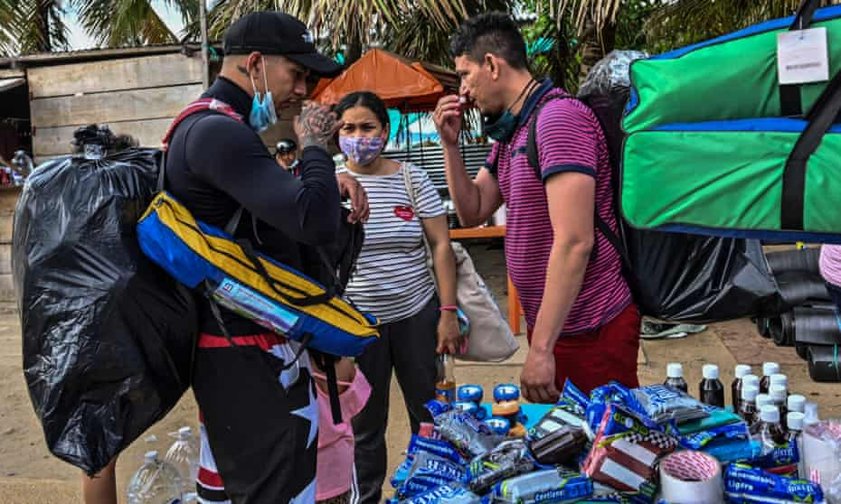 Migrants from Venezuela in Necoclí check the smell of a poison they buy for their journey in the Darién Gap.