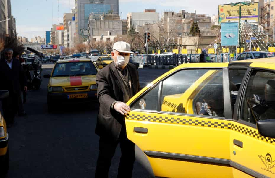 A man wearing face mask and protective gloves leaves a Taxi in Tehran 2 March