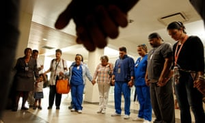 Hospital employees and nurses gather to pray for a co-worker who was critically injured in a violent attack during the chaos post-Maria.
