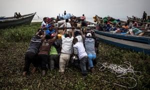 People pushing boat out at Lake Albert, DRC.