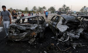Residents gather at the site of a car bomb attack in the mainly Shiite district north of Baghdad on Saturday.