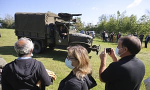 People watch World War II history enthusiasts in Normandy, on the eve of its 77th anniversary.