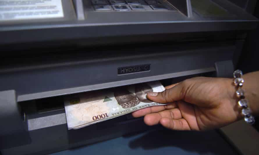 A customer withdraws Nigerian naira from an ATM at a bank in Asaba, Delta State, Nigeria.