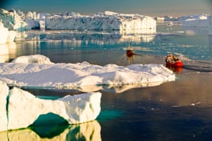 Tourist boat trips sail through icebergs at midnight from the Jacobshavn glacier, Greenland