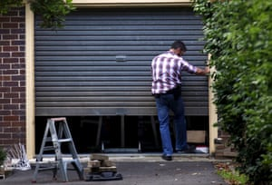 An Australian Federal Police officer enters the garage of Craig Wright in Sydney. Police said the raid was not linked to claims Wright was involved with bitcoin.
