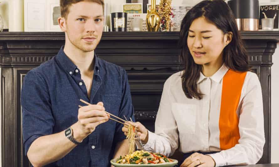 Jordan Bourke and Rejina Pyo eat from one plate using chop sticks