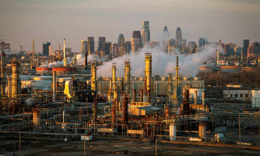 The Philadelphia Energy Solutions oil refinery is seen at sunset in front of the Philadelphia skyline.