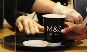 An assistant serves coffee in a Marks & Spencer cafe as they reopen for takeaways on 14 May.