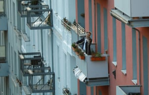 A man plays the violin from a balcony to raise morale as German government is preparing to close borders and schools