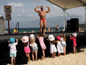 A bodybuilder flexes in front of a line of young girls