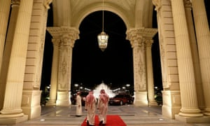 Men walk out of the entrance of the Ritz-Carlton hotel in Riyadh
