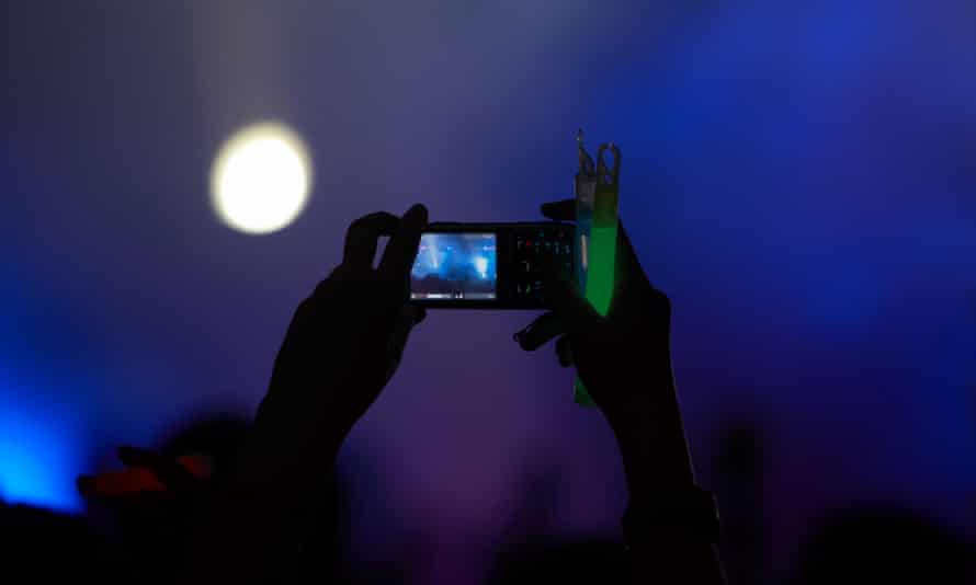 Screen saver … A fan films a show on their phone.