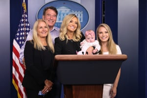 McEnany holds her daughter Blake while posing with her parents Mike and Leanne McEnany and younger sister Ryann McEnany at the podium in the Brady Press Briefing Room.