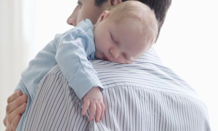 Father holds newborn baby on shoulder