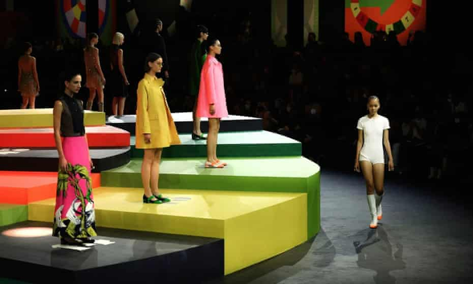 Models wearing yellow, pink and white mini dresses stand on a yellow, green and black stage