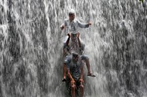 Mumbai, India Boys play under an overflowing dam along Powai Lake after heavy rain