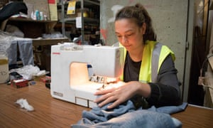 A volunteer sews the seams up on a pair of jeans at a Calais warehouse shared by charities.