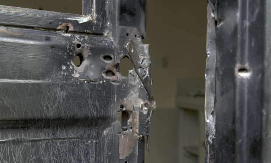 Bullet holes in a metal door that was shot open at the Terrain compound after it was looted.