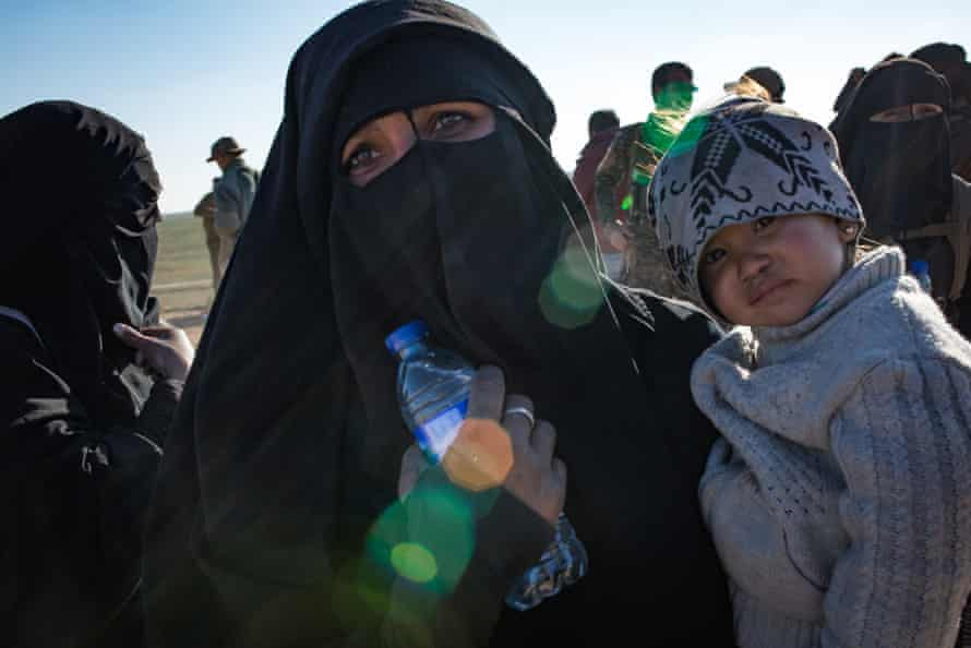 A Ukrainian woman from Crimea seen holding her young boy at a civilian screening point, after fleeing heavy fighting in the city of Baghuz, on 12 February 2019