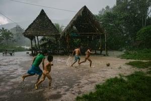 Children play football under torrential rain in Soledad
