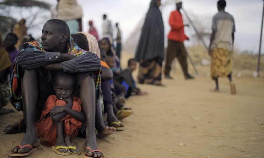 A Somali father sits with his daughter at a registration centre, having been displaced from their home in southern Somalia by famine