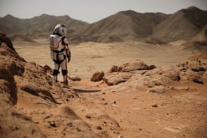 A staff member wearing a mock space suit poses in the Gobi desert near the C-space project Mars simulation base outside Jinchang.
