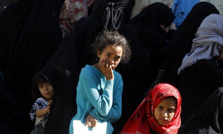 Conflict-affected Yemeni children wait to receive food rations provided by a local charity amid severe food insecurity in Sana'a