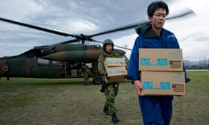 Boxes of bottled water are unloaded from a Japanese military helicopter