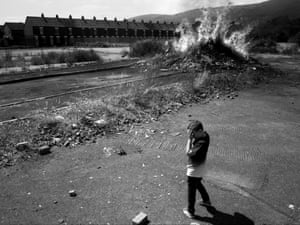 A boy turning away from rubbish on fire at a wasteland on Caledon Street, 2018