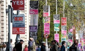 People cross the road past posters urging a yes vote in the referendum to repeal the eighth amendment of the Irish constitution and posters calling for a no vote